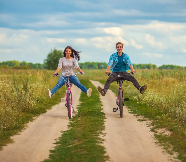 The happy couple ride a bicycle in a field