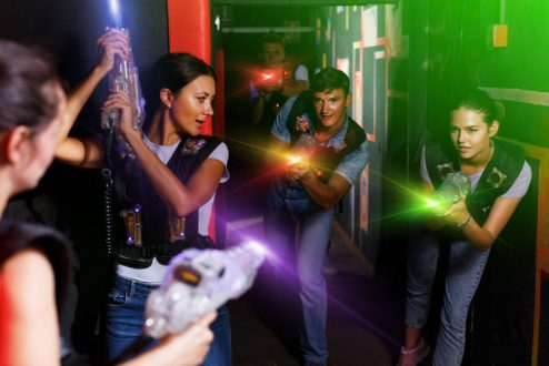 Portrait of active young friends standing with laser guns during laser tag game in dark room